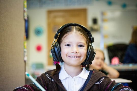 Child in headphones illustrates one type of Speech Generating Device available at AAC Speech Clinic LLC