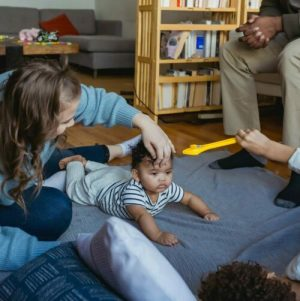 Physical therapist holding a baby to illustrate in-home physical therapy.